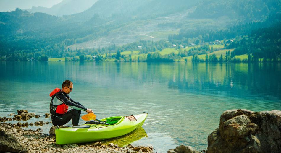 Man sitting by kayak at lakeshore
