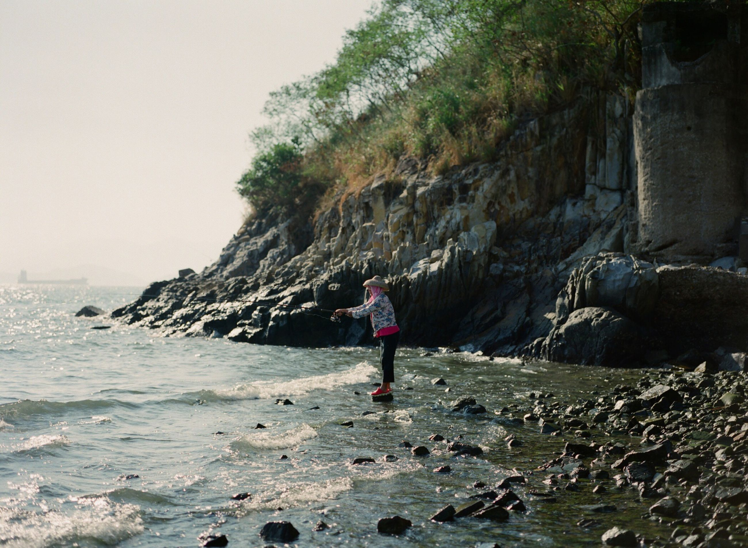 lifestyles, water, leisure activity, full length, rock - object, rear view, sea, standing, casual clothing, rock formation, scenics, person, beauty in nature, tranquil scene, beach, tranquility, nature, vacations