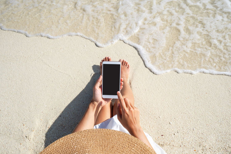 High angle view of man using mobile phone at beach