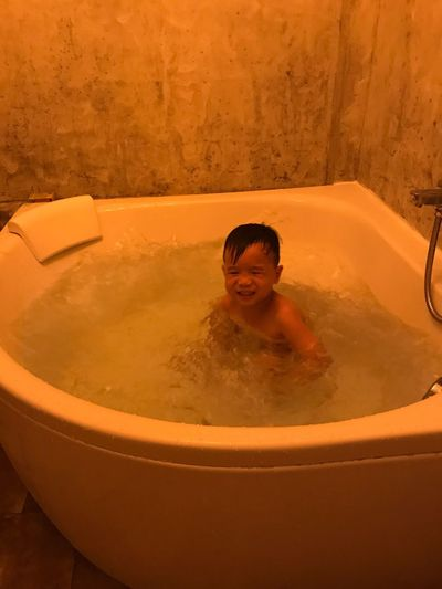 Boy taking bath in tub at home