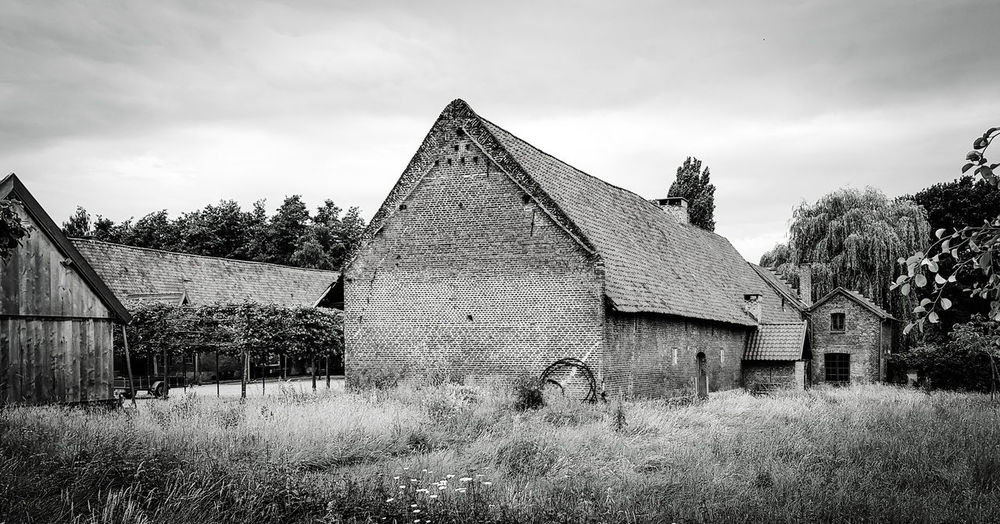 Old building on field against sky