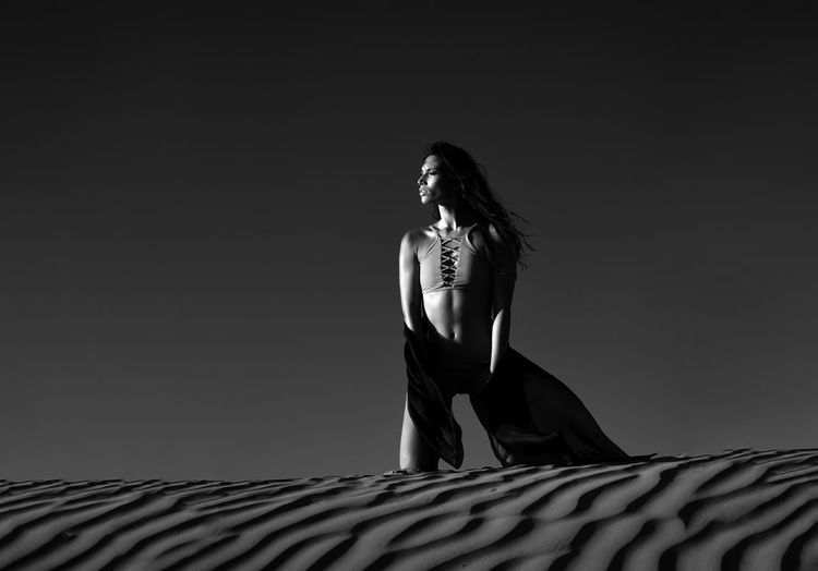 Low angle view of woman looking away on sand against sky