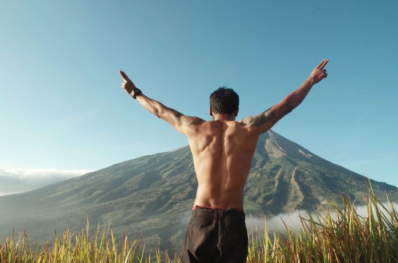 Rear view of shirtless man standing against mountain