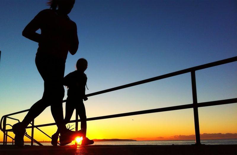 Silhouette friends jogging on beach at sunrise