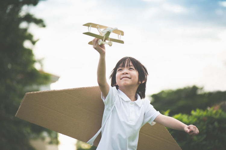 Cheerful by wearing cardboard wings while holding model airplane against sky