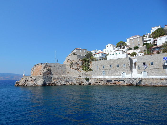 Houses by sea against clear sky ay hydra