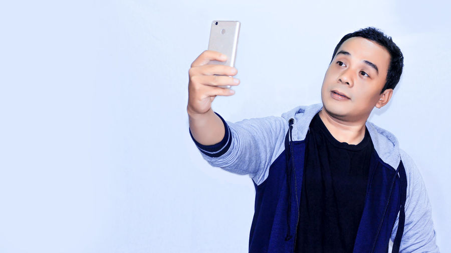 Portrait young asian mas selfie with his smartphone
