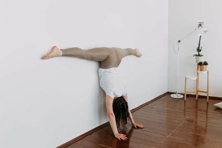 Full length of man skateboarding on hardwood floor against wall