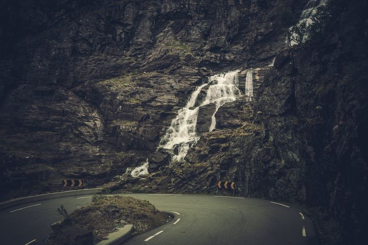 Scenic view of waterfall on mountain by winding road