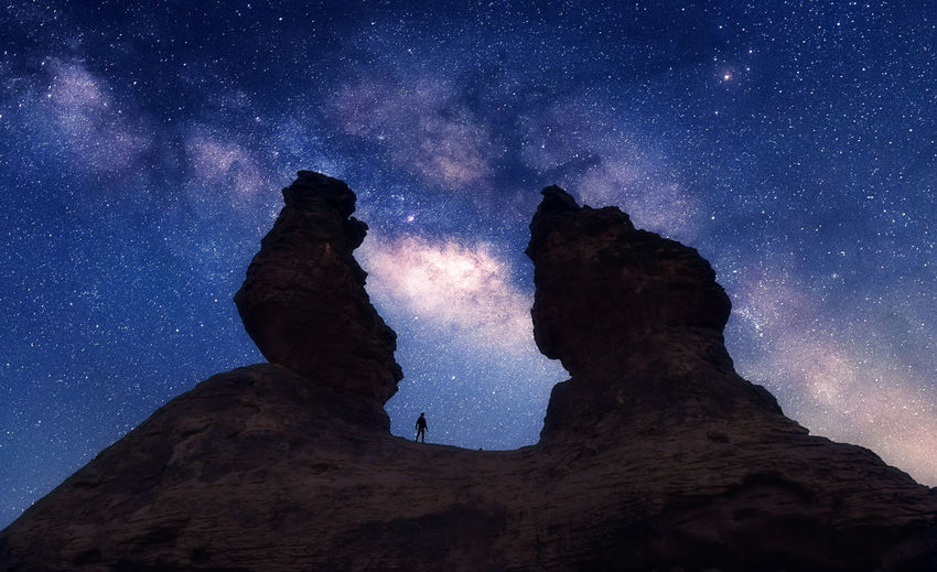 Low Angle View Of Silhouette Man On Rock Formation Against Star Field At Night