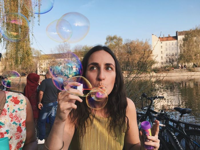 Portrait Of Young Woman With Bubbles Against Sky