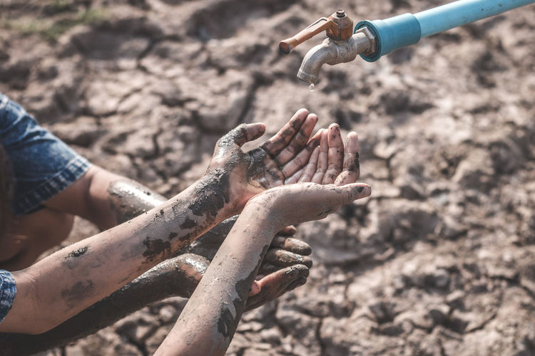 Cropped Dirty Hands Below Faucet On Barren Land During Drought