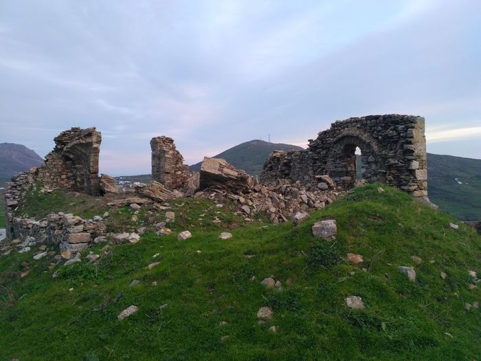Old ruins on green mountain against sky