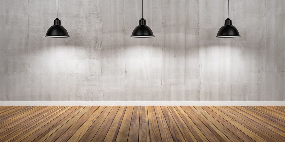 Illuminated lamp hanging on floor against wall
