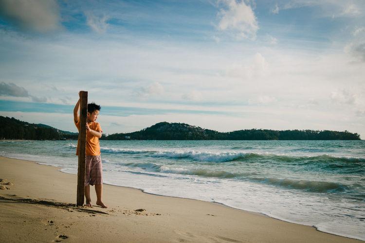 Full length of boy standing on beach against sky