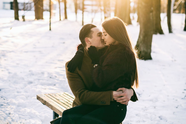 Adult Adults Only Beauty Beauty In Nature Cold Temperature Couple - Relationship Flirting Happiness Love Men Nature Outdoors Romance Sitting Snow Sunlight Togetherness Two People Warm Clothing Winter Women Young Adult Young Couple Young Women