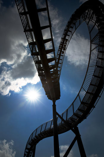 Low angle view of silhouette ferris wheel against sky