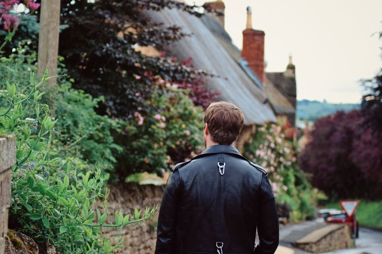 Rear view of man standing by plants against building
