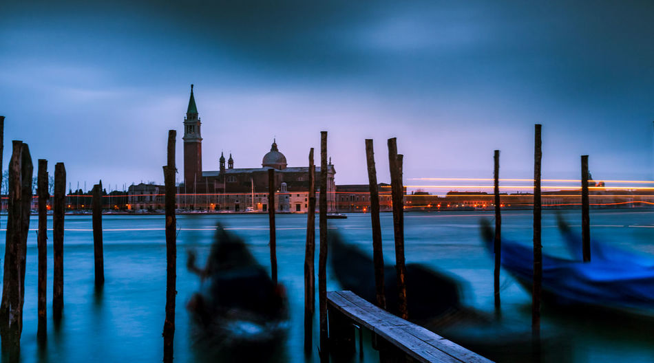 Wooden posts in grand canal at dusk