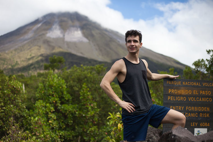 Smiling young man standing by sign against volcano