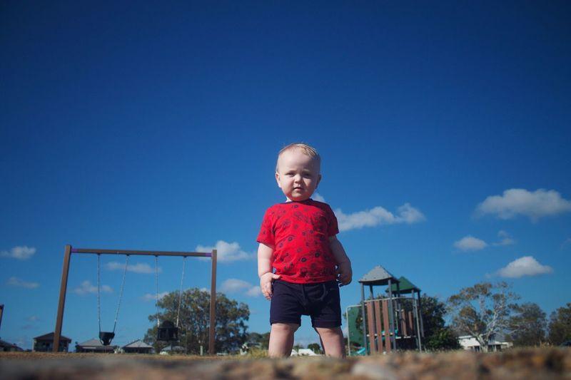 Portrait of boy standing on land against blue sky