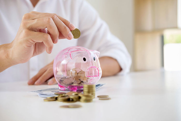 Midsection of businessman inserting coin in piggybank
