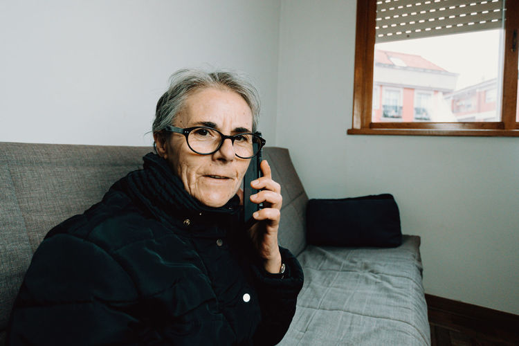 Portrait of mature woman talking phone at home