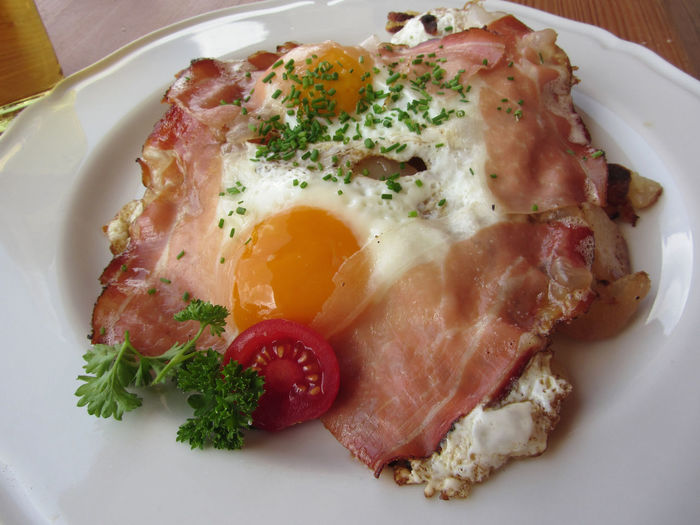 Typical South Tyrolean dish with speck, fried eggs, potatoes and chive . View from above Speck Above Tyrol Potato Egg Chive Food Fried Alto Adige Tyrolean Smoked Bacon Ham Cold Cuts Snack Cut Appetizing  Dine Speciality Rustic Eat Tasty SLICE Hot Gourmet