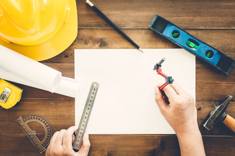 Cropped hands of architect preparing blueprint amidst various tools on wooden table