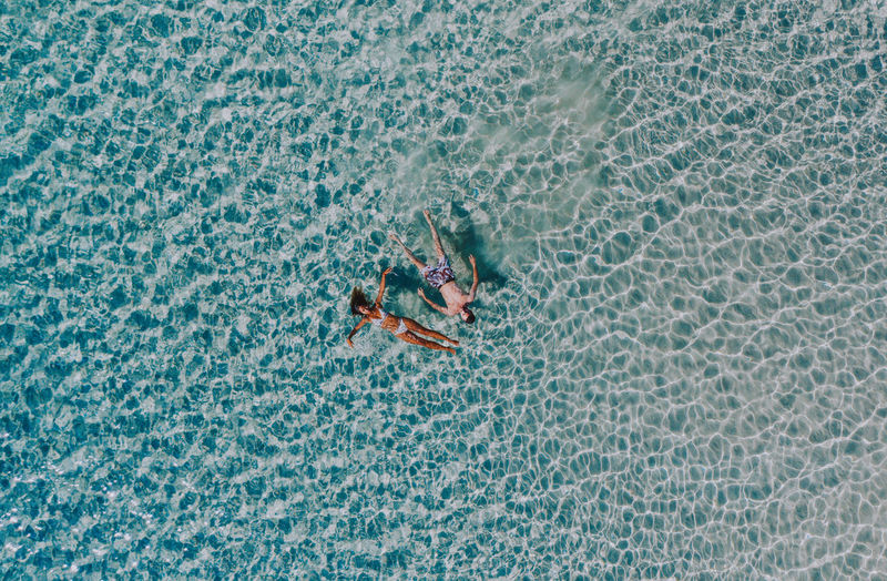 Drone view of couple swimming in sea on sunny day