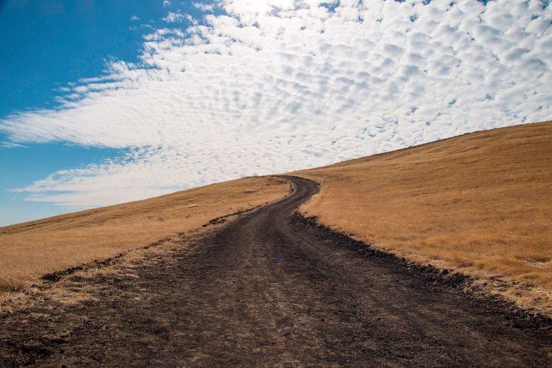 Tire tracks on road against sky