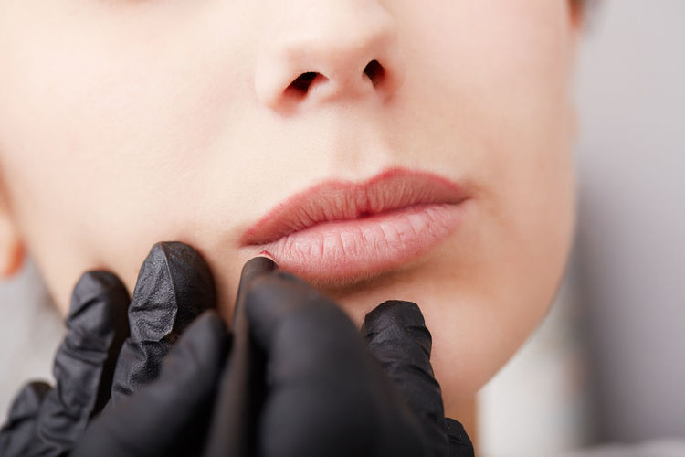 Cropped hands of beautician treating woman lips