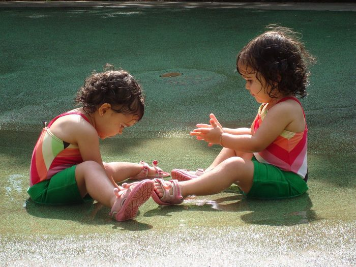 Twin baby girls playing in water on floor