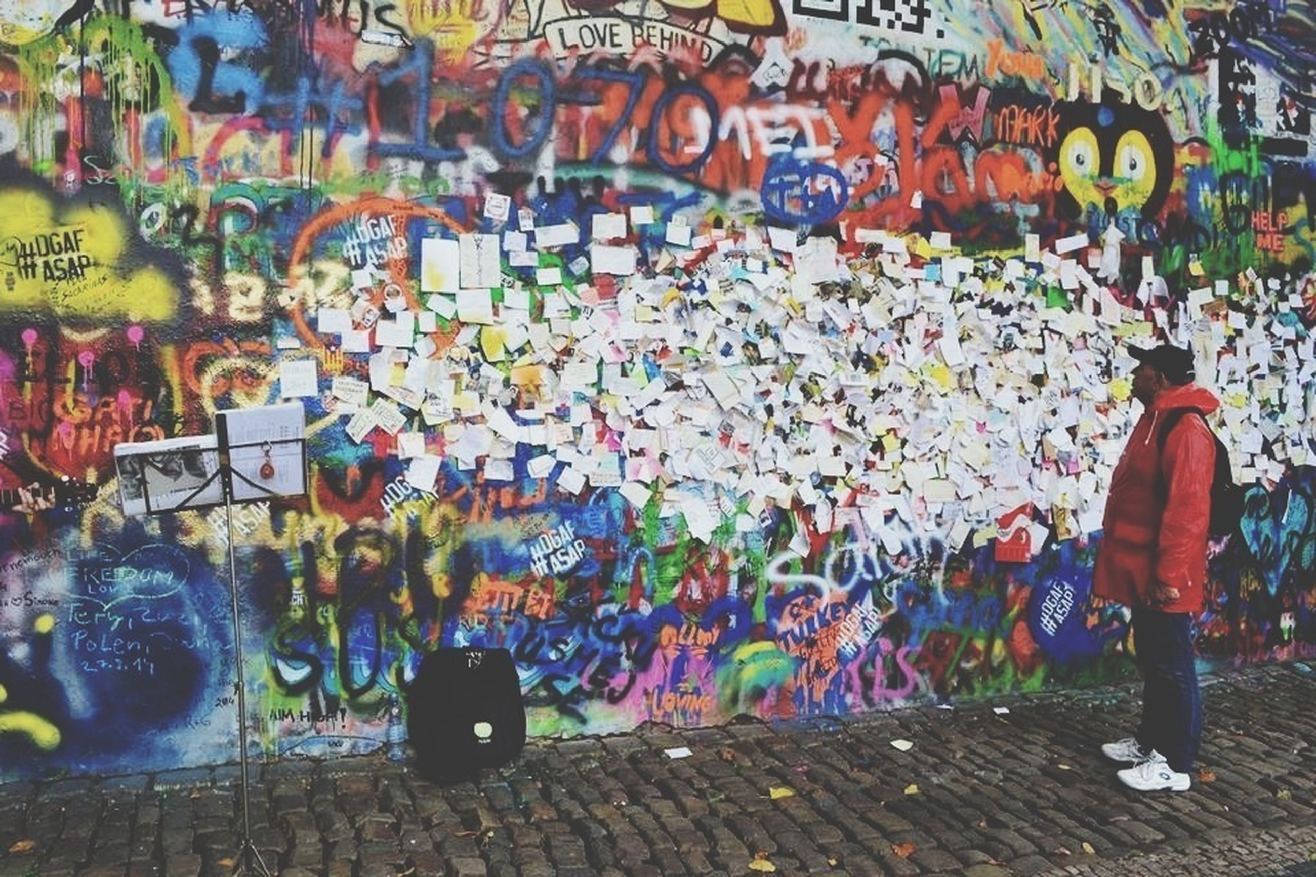 lifestyles, person, leisure activity, multi colored, men, graffiti, street, standing, rear view, casual clothing, walking, full length, wall - building feature, text, built structure, large group of people, illuminated