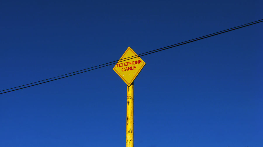 Low Angle View Of Sign Board By Cable Against Clear Blue Sky