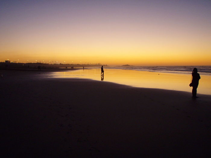 Silhouette man standing on beach against clear sky at sunset