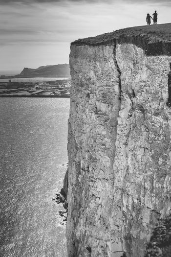 Low section of man standing on cliff by sea against sky