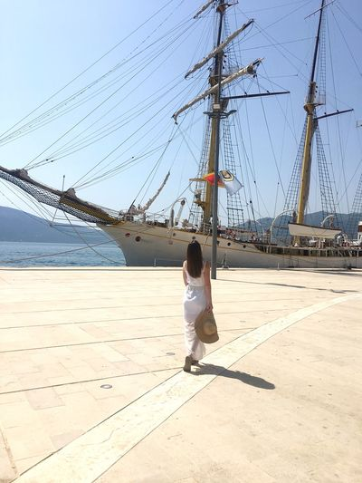 Rear view of woman standing at harbor against sailboat
