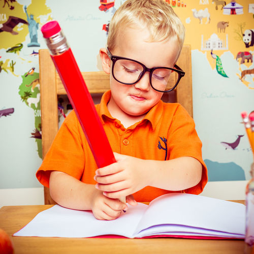 Boy writing in book with large pencil in school