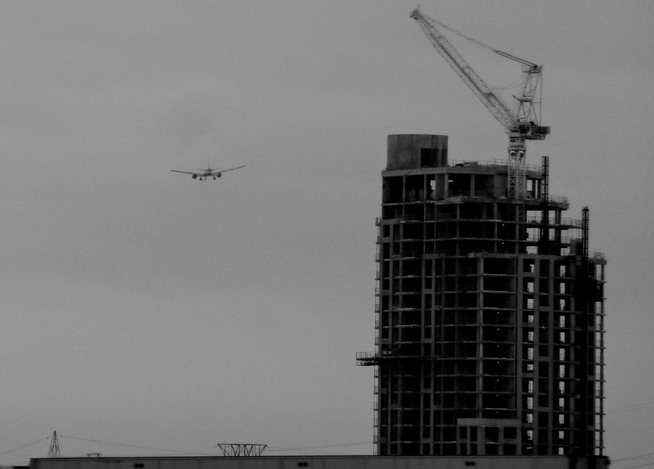 development, architecture, construction site, transportation, flying, no people, outdoors, sky, building exterior, day, low angle view, clear sky, airplane