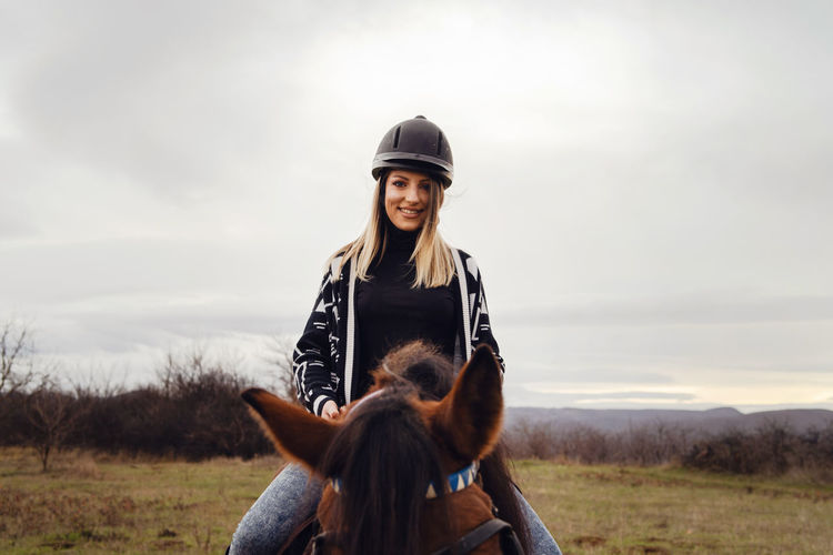 View of woman wearing helmet riding horses on field