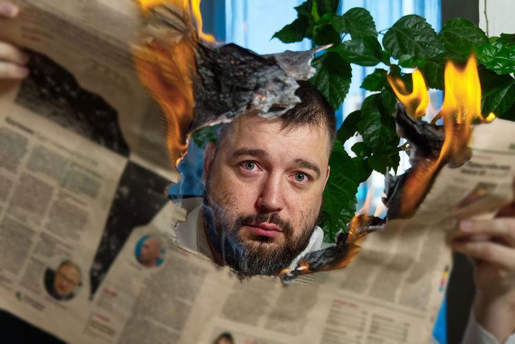 Portrait of man burning newspaper