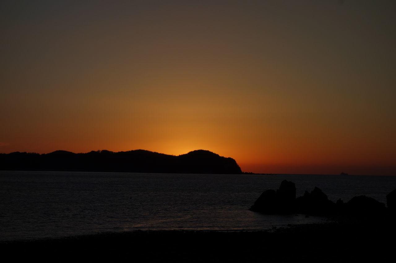 Silhouette Of Coastline At Sunset