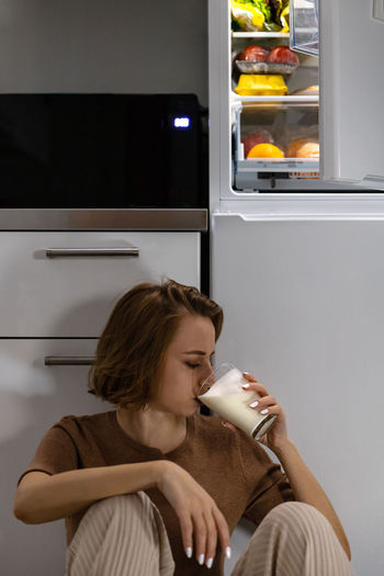 Woman drinking milk while sitting against cabinet at home