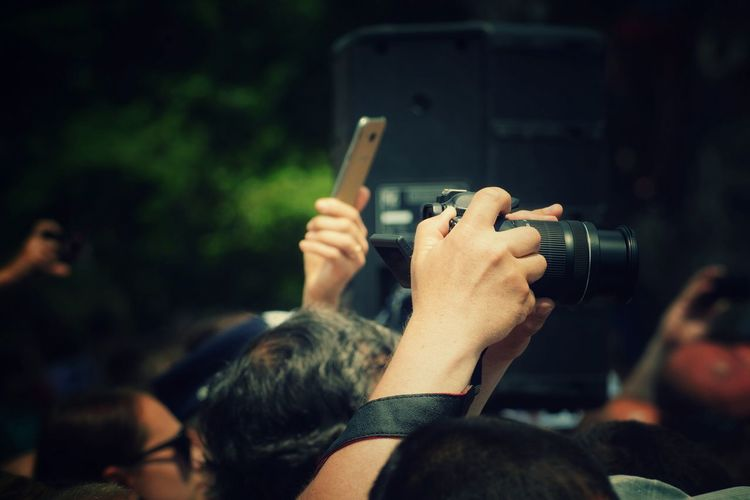 Copped hand of person photographing amidst crowd