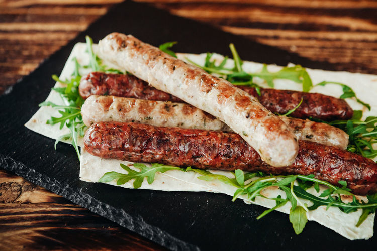 Close-up of roasted sausages with leaf vegetables on slate