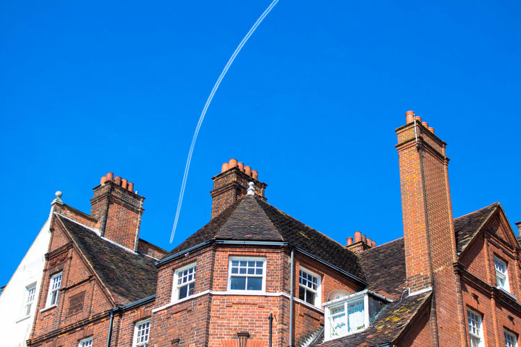 Low angle view of old building against vapor trail in clear blue sky