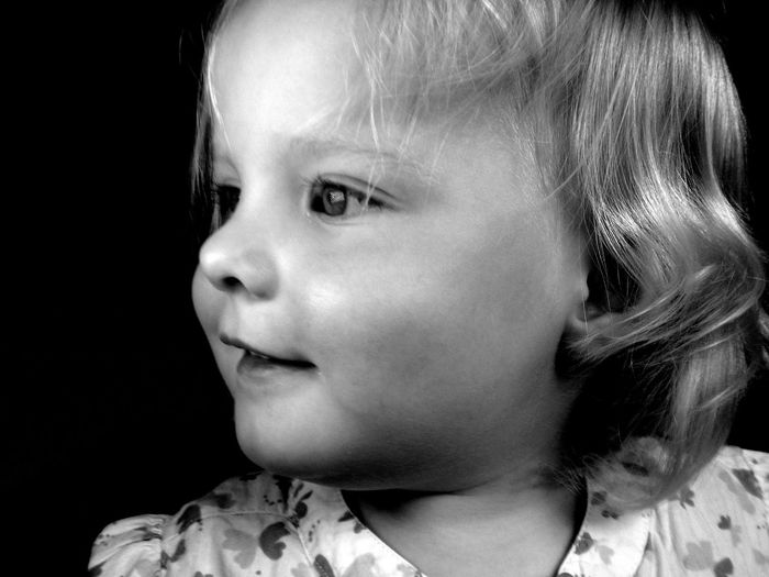 Close-up portrait of cute girl looking away against black background