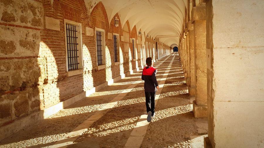 Rear view of boy running in corridor