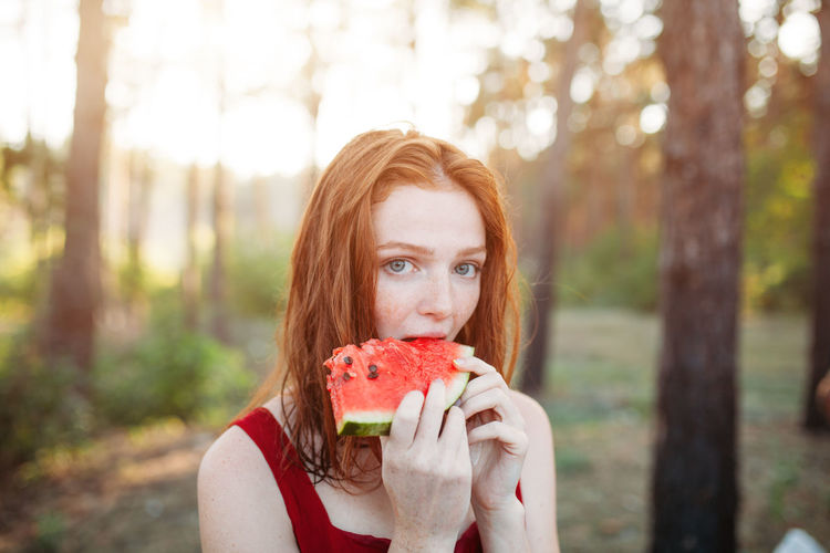 Beautiful redhead woman eat watermelon on the nature. Red hair girl with melon. Summer time Portrait Fruit Food And Drink Food Healthy Eating One Person Redhead Looking At Camera Wellbeing Headshot Healthy Lifestyle Eating Holding Freshness Hairstyle Front View Tree Long Hair Hair Outdoors Watermelon Melon Summer Summertime Eating Eat Berry Fruit Vitamin Forest Wood Close-up